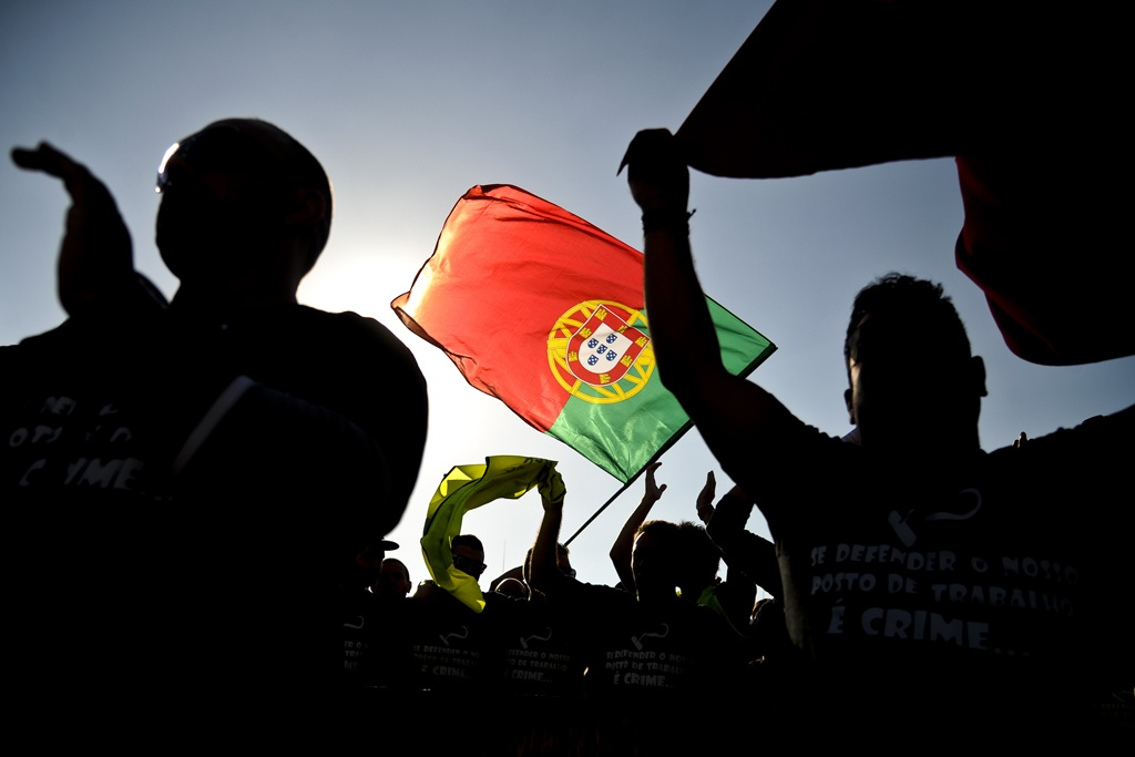 People wave the Portuguese flag during a protest against government's austerity policies at the Terreiro do Paco Square in Lisbon on September 29, 2012. Thousands of Portuguese took to the streets of Lisbon today in a new protest against government financial policies expected to get even tougher to meet pledges to creditors. AFP PHOTO/ PATRICIA DE MELO MOREIRA (Photo credit should read PATRICIA DE MELO MOREIRA/AFP/GettyImages)